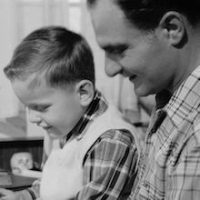 circa 1956:  A son reads with his father.  (Photo by Three Lions/Getty Images)